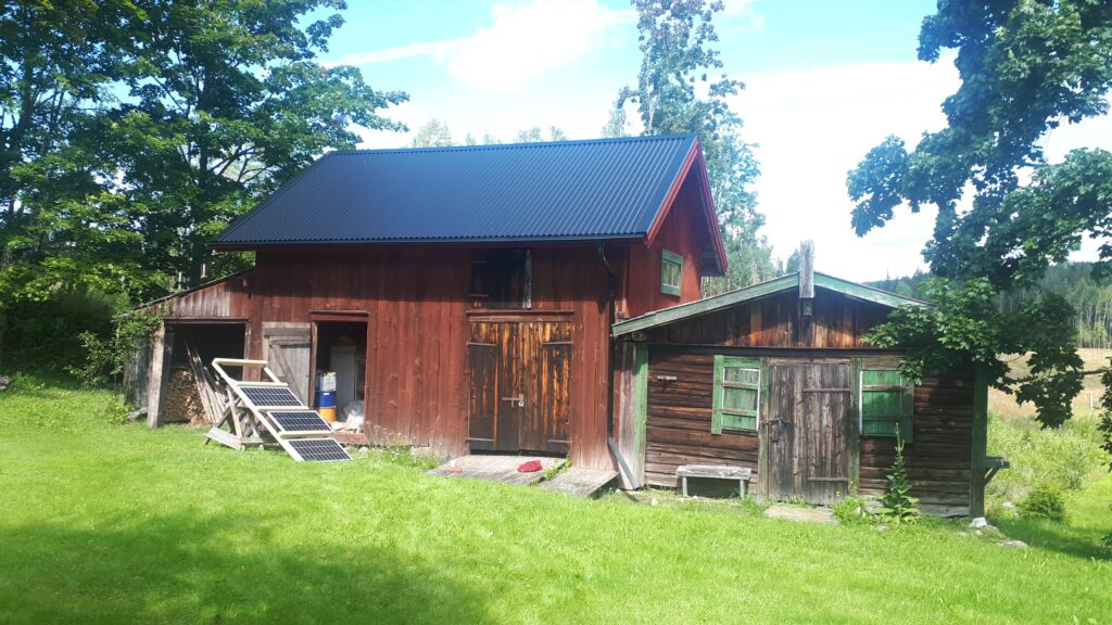 Off-grid solar panels outside an old barn